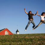 Millennial couple jumping with joy with house as background