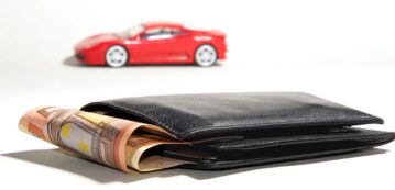 Photo of a red car near a black wallet