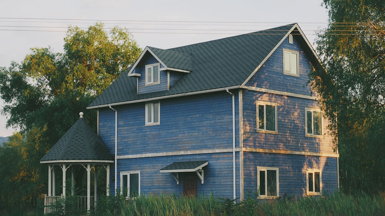 two storey blue house surrounded by trees