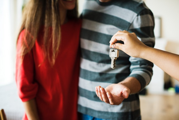 person giving home keys to a couple