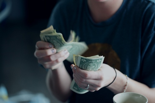 A woman counting dollar bills.